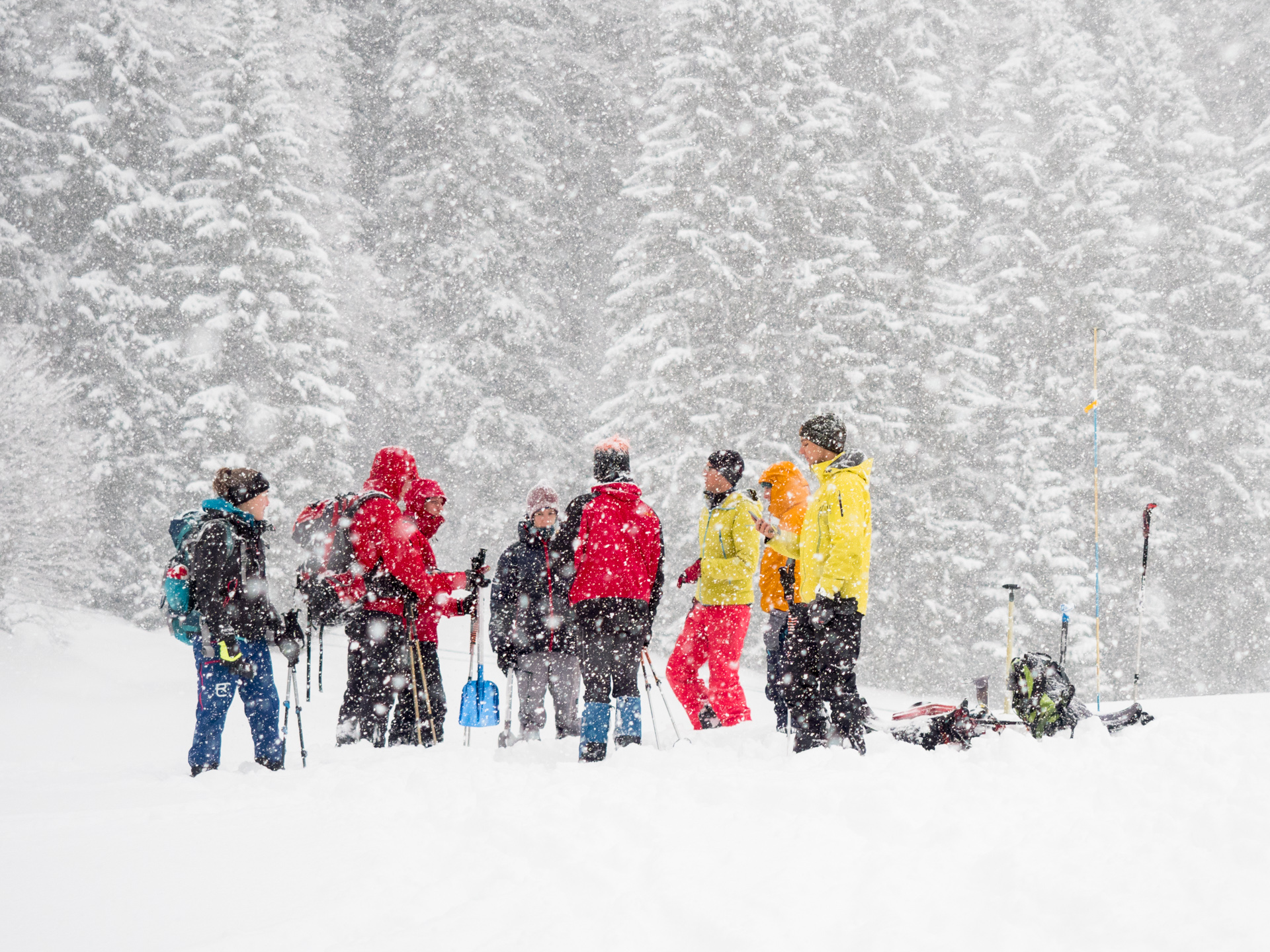 Group of people listening to instructor during heavy snowfall